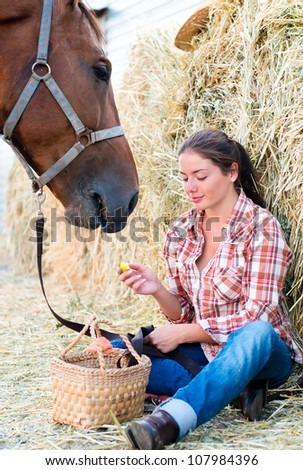 Girl and her horse resting near a haystack - stock photo