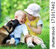 girl and her little brother playing with  dog on  grass - stock photo