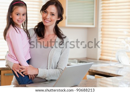 Girl and her mother using a notebook in a kitchen