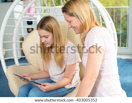 girl and her mother using tablet PC together - stock photo
