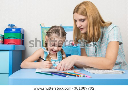Girl and mother fun in a notebook draw - stock photo