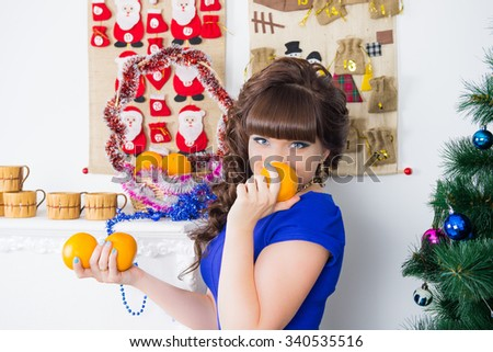 Girl and orange. Portrait of a young beautiful woman with orange. Christmas food, fruit for the Christmas menu, a diet before Christmas. premonition Christmas in the interior of the house
