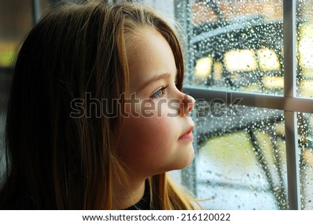 Girl and rain wet glass autumn bad weather.