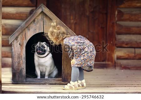 girl and small dog, dog house - stock photo