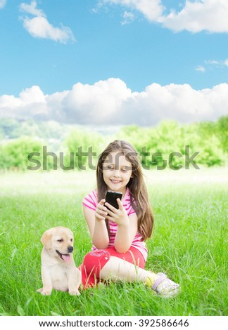 Girl and smartphone and labrador puppy