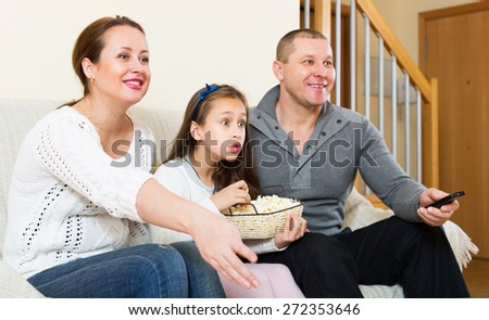 Girl and smiling parent sitting with popcorn in front of TV. Focus on girl - stock photo
