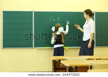 Girl and teacher near chalkboard solve simple math examples in classroom at school. Girl writes. - stock photo