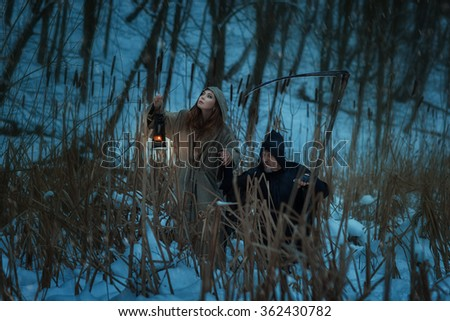 Girl and the dwarf death go on winter snow-covered forest. - stock photo