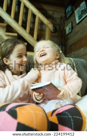 Girl and toddler sitting on couch, laughing - stock photo