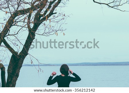 Girl and tree on the lake in autumn time