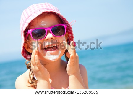 Girl anoints her face protective cream on the beach - stock photo