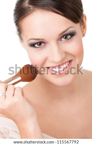 Girl applying cosmetics to her face with the help of cosmetic brush, isolated on white - stock photo