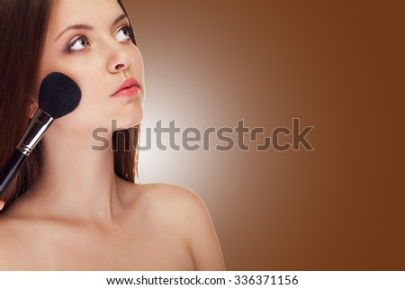 Girl applying make up with brush on brown background in studio photo. Make up addiction. Clean healthy skin