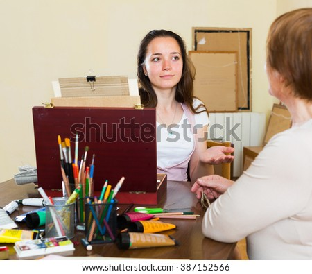 Girl artist  painting  portrait of woman at workshop - stock photo