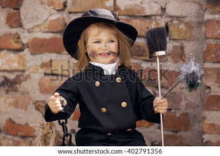 Girl as a chimney sweep against brick wall.  - stock photo