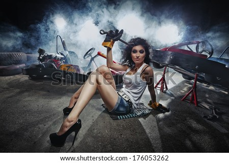 Girl at a garage next to the Go-kart  in smoke - stock photo