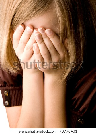 girl at age of thirteen covers her face with her hands closeup - stock photo