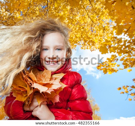 Girl at autumn. Child with leaf at park