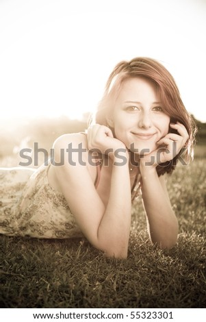 Girl at grass field at sunset. Photo in old image style. - stock photo