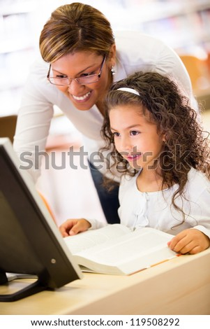 Girl at school with her teacher learning to use technology - stock photo