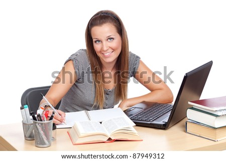 Girl at table, studying and smiling - stock photo