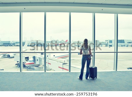 Girl at the airport window - stock photo