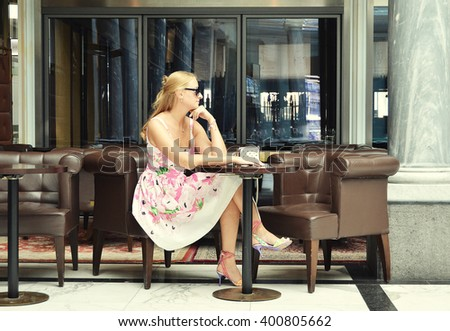 Girl at the cafe table - stock photo