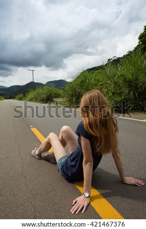 girl at the empty brazilian road at sunny cloudy day