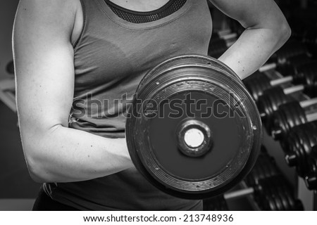 Girl at the gym. Hand holding a dumbbell. Girl doing exercises with dumbbell. Sports, fitness, dumbbell, gym - Concept of force, sport, health. Article about bodybuilding.