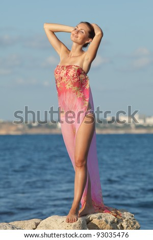 Girl at the sea. Attractive young woman is posing on background of sea. Lady in pink sarong with arms raised on the beach - stock photo