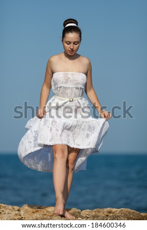 Girl at the sea. Barefoot young woman in white walks on rocky seashore - stock photo