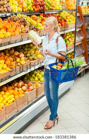 Girl at the shop choosing fruits and vegetables hands cabbage and full of purchases hand cart - stock photo