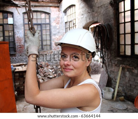girl at work on a construction site, holding a chain - stock photo