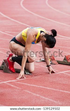 Girl athlete preparing to start on the treadmill - stock photo