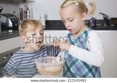 Girl baking cookie while brother tasting batter in kitchen - stock photo