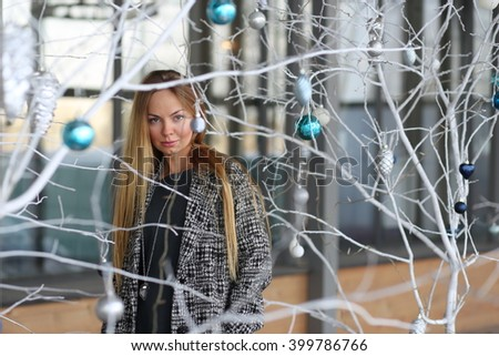 Girl behind the tree with Christmas toys - stock photo