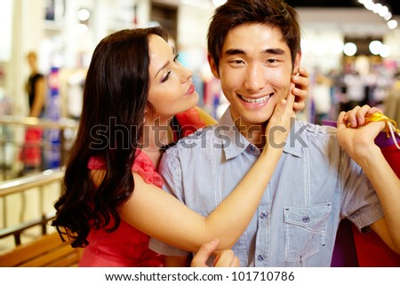 Girl being about to kiss her boyfriend smiling at cam, shopping series