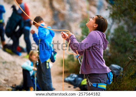 girl belayer with the rope and carabines - stock photo