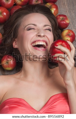 Girl biting apple and laughs - stock photo