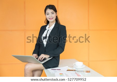 Girl black suit At a desk in the office.