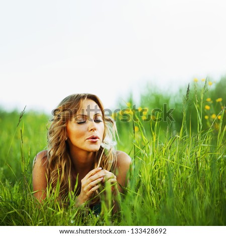 girl blow on dandelion on green field