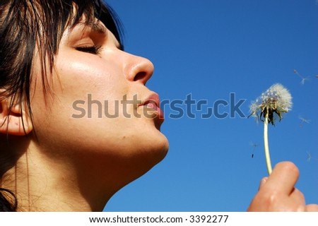 girl bloweing dandelion - stock photo