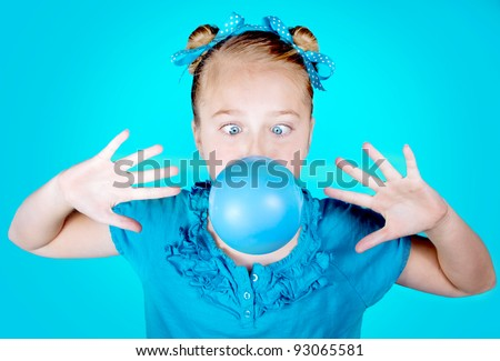 Girl blowing a blue bubble gum on blue background - stock photo