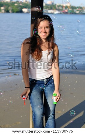 Girl blowing bubble near the river - stock photo