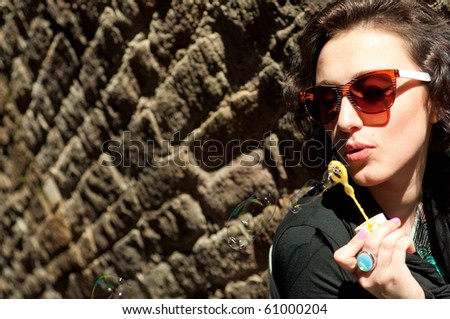 Girl blowing bubbles at the wall - stock photo