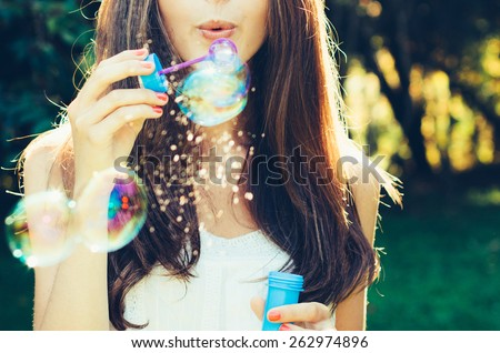 Girl blowing bubbles outdoor. Focus on lips. - stock photo