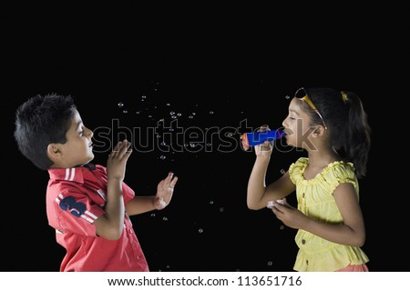 Girl blowing bubbles towards a boy - stock photo