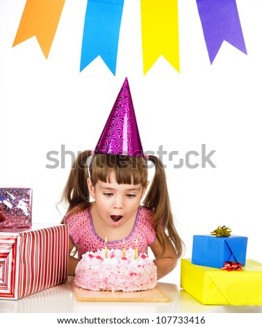 girl blowing candles on her cake. isolated over white background