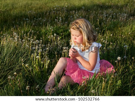 Girl blowing danelion in a field of grass