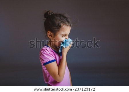girl blowing his nose into a handkerchief - stock photo